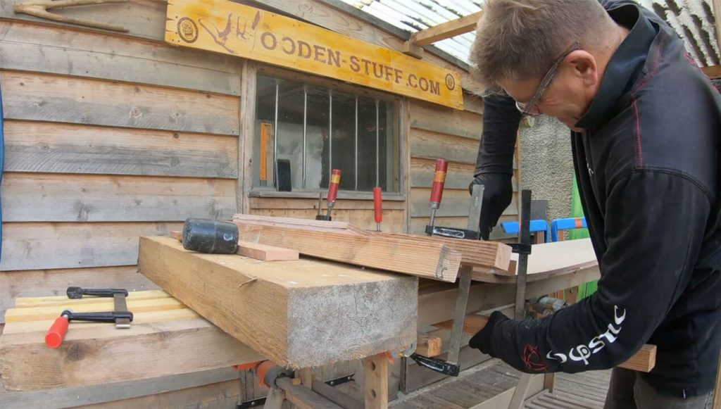 The use of G-clamps to press the wooden sheets together to form the gradual curvature of the blank