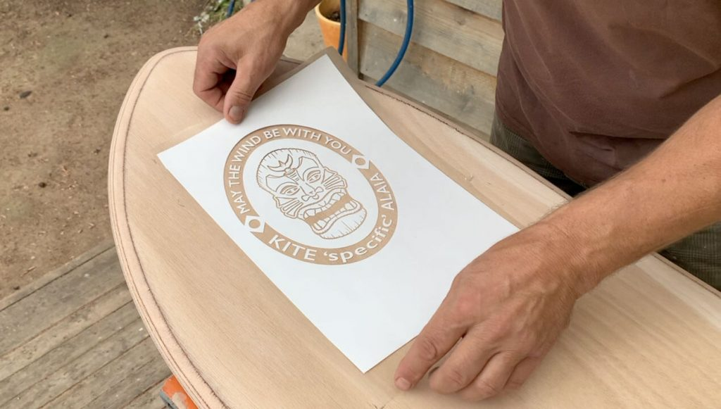 Sticking the vinyl template in position to create the logo